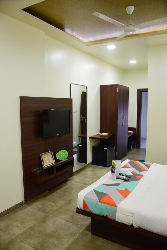 Well appointed room at Global Inn - TV, mini-fridge, mirror, wardrobe, shoe rack etc.