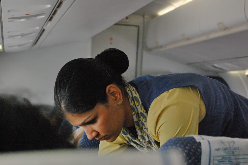 यात्री की सीट बेल्ट कसती हुए एयर होस्टेस