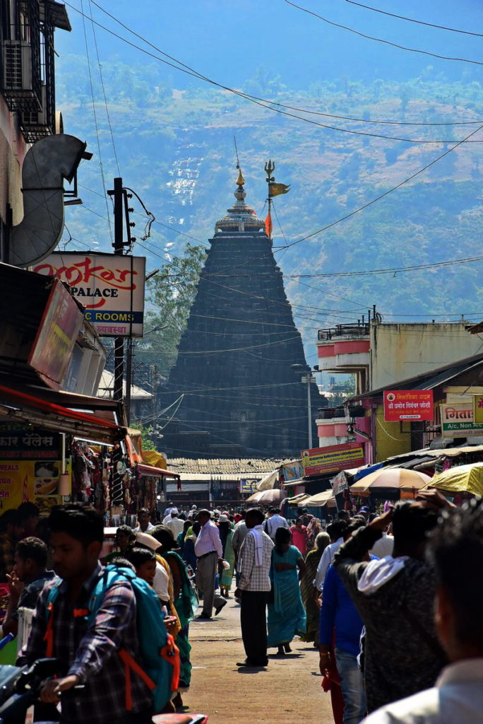 पार्किंग से त्र्यंबकेश्वर मंदिर का गुम्बद और उसके पीछे त्र्यंबक पर्वत दिखाई देते हैं।